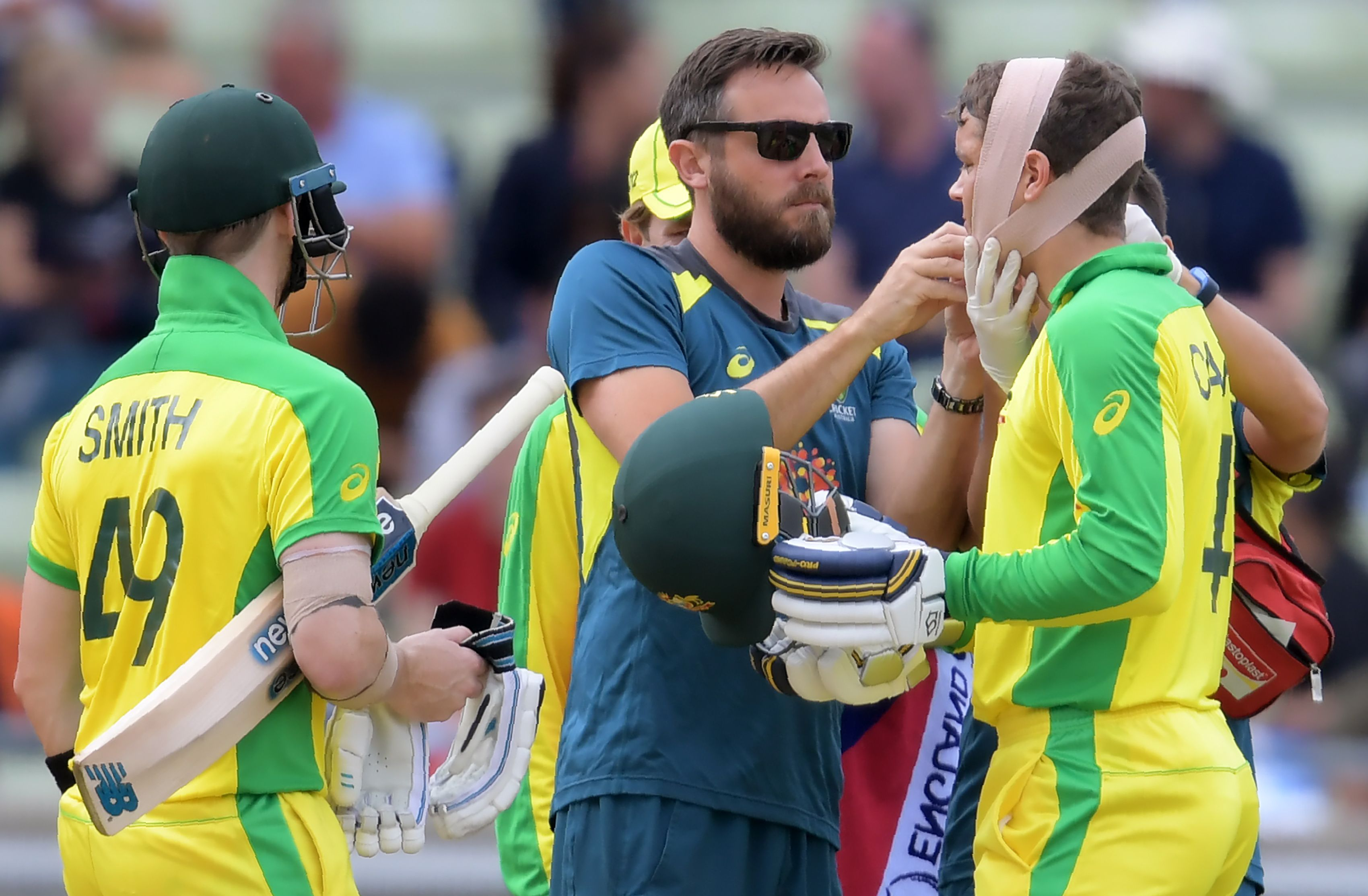 Alex Carey (R) receives continued medical attention after he was his by a bouncer. Photo: AFP